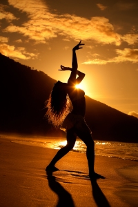 silhouette of woman dancing at the beach during sunset